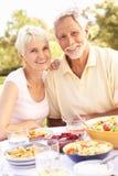 Ältere Paare, die Mahlzeit im Garten genießen Stockfoto