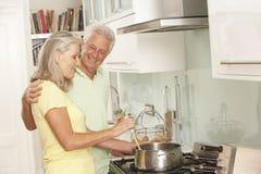 Ältere Paare, die Mahlzeit am Kocher vorbereiten Lizenzfreie Stockfotografie