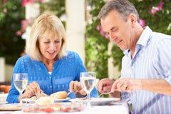 Ältere Paare, die Mahlzeit outdoorss genießen Lizenzfreie Stockbilder