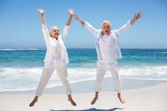 Ältere Paare, die mit den angehobenen Armen springen Stockfoto