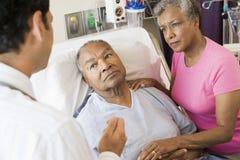 Ältere Paare, die mit Doktor sprechen Stockbilder