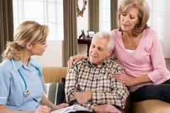 Ältere Paare, die mit Gesundheits-Besucher sprechen Stockfotografie
