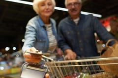 Ältere Paare, die mit Handy zahlen lizenzfreies stockfoto