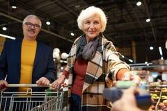 Ältere Paare, die mit Telefon zahlen lizenzfreies stockfoto