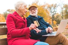 ältere Paare, die online mit Laptop und Kreditkarte beim Sitzen auf Bank kaufen lizenzfreie stockbilder
