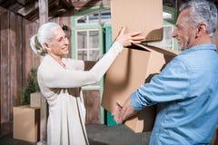 Ältere Paare, die Pappschachteln beim Bewegen in neues Haus halten stockbilder