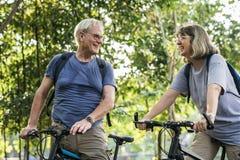 Ältere Paare, die am Park radfahren Lizenzfreie Stockbilder