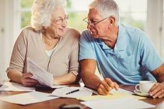 Ältere Paare, die Rechnungen zählen Stockbild