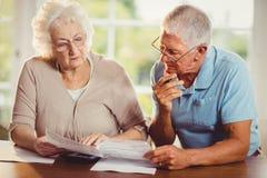 Ältere Paare, die Rechnungen zählen Lizenzfreies Stockbild