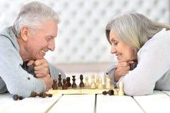 Ältere Paare, die Schach spielen lizenzfreies stockfoto