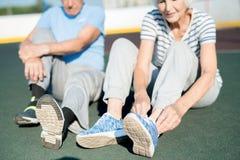 Ältere Paare, die Schuhe auf Bahn binden lizenzfreies stockbild