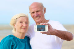 Ältere Paare, die Selbstfoto auf dem Strand machen Stockfoto