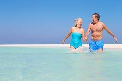 Ältere Paare, die Spaß im Meer am Strand-Feiertag haben Stockfotografie