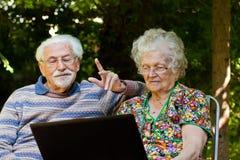 Ältere Paare, die Spaß mit dem Laptop draußen haben stockbild