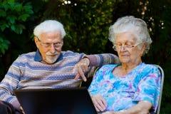 Ältere Paare, die Spaß mit dem Laptop draußen haben lizenzfreies stockfoto
