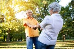 Ältere Paare, die Spaß und Tanz im Park haben stockfotografie