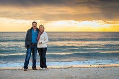 Ältere Paare, die am Strand stehen Stockbild