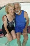 Ältere Paare, die am Swimmingpool sitzen Stockfotos