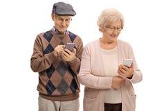 Ältere Paare, die Telefone betrachten Stockbild