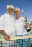 Ältere Paare, die Trophäe am Tennis-Netz halten Stockbilder