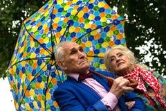 Ältere Paare, die unter einen Regenschirm im Regen gehen unterhaltung Stockbild