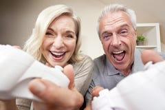 Ältere Paare, die videokonsolen-Spiel spielen Stockbilder