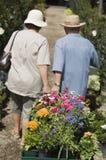Ältere Paare, die Wagen der Blumen ziehen Stockbilder
