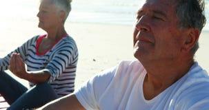 Ältere Paare, die Yoga am Strand tun stock video footage