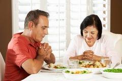 Ältere Paare, die zu Hause Anmut vor Mahlzeit sagen Stockfotografie