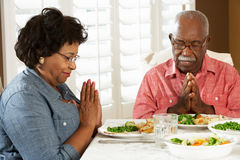 Ältere Paare, die zu Hause Anmut vor Mahlzeit sagen Lizenzfreies Stockbild