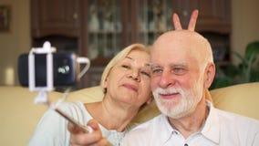 Ältere Paare, die zu Hause auf Couch sitzen Herstellung von selfie mit Smartphone und selfie Stock stock video footage