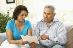 Ältere Paare, die zu Hause Finanzdokument studieren Stockbilder