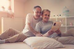 Ältere Paare, die zu Hause genießen und Lesebuch bevor dem Schlafen stockfotos