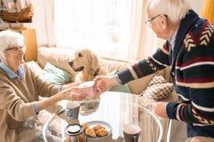 Ältere Paare, die zu Hause Geschenke austauschen stockfotos