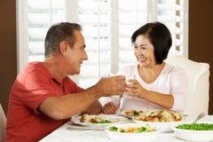 Ältere Paare, die zu Hause Mahlzeit genießen Stockfoto