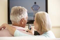 Ältere Paare, die zu Hause mit großem Bildschirm fernsehen Stockfotografie