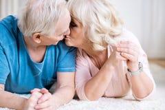 Ältere Paare, die zusammen auf Teppich und dem Küssen liegen stockfoto