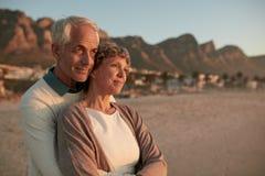 Ältere Paare, die zusammen stehen und auf dem Strand umfassen lizenzfreies stockfoto