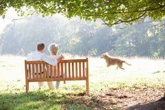 Ältere Paare draußen mit Hund Stockfotografie