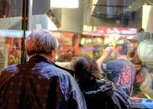 Ältere Paare, ein Restaurantmenü in einem Fenster zu betrachten gesehen stockfotografie
