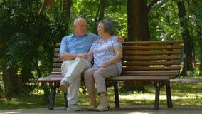 Ältere Paare entspannten sich die Unterhaltung auf der Parkbank stock video