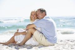 Ältere Paare am Feiertag, der auf Sandy-Strand sitzt Stockfotografie
