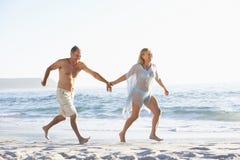 Ältere Paare am Feiertag, der entlang Sandy Beach Looking Out To-Meer läuft Stockfotos