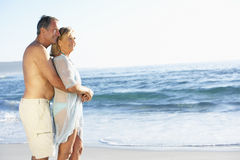 Ältere Paare am Feiertag, der entlang Sandy Beach Looking Out To-Meer läuft Lizenzfreie Stockbilder
