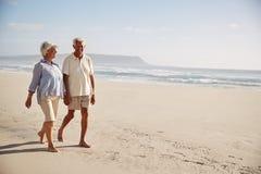 Ältere Paare im Ruhestand, die Hand in Hand entlang Strand zusammen gehen lizenzfreie stockfotos