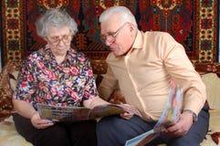 Ältere Paare lasen die Nachrichten Stockbilder