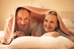Ältere Paare liegen zusammen unter den Abdeckungen Stockbilder