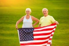 Ältere Paare mit amerikanischer Flagge Stockbilder