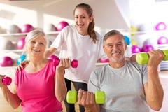 Ältere Paare mit einem persönlichen Trainer stockbild