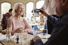 Ältere Paare mit Kellner Paying Bill In Restaurant lizenzfreie stockbilder